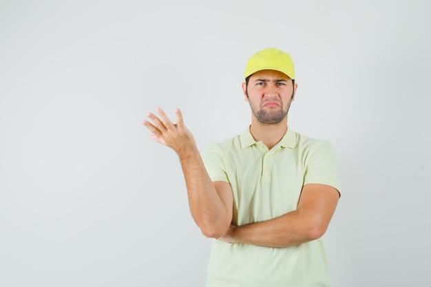 手を上げて混乱している黄色の制服を着た配達人、正面図。