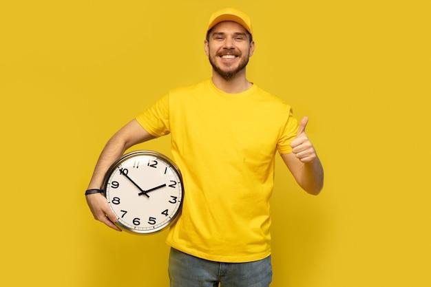 黄色の作業服の配達人は、黄色の背景のスタジオの肖像画に分離された時計を保持します。