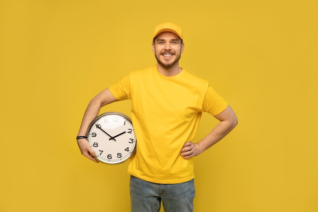 黄色の作業服の配達人は、黄色の壁のスタジオの肖像画に分離された時計を保持します