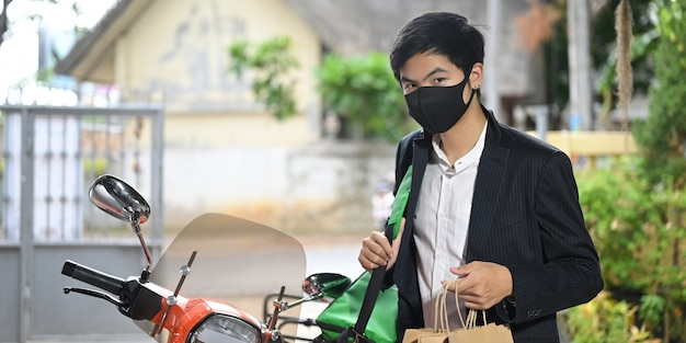 A delivery man is holding a parcel bag while standing next to his motorcycle.
