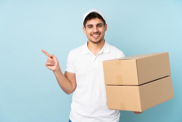 Доставка человек, изолированные на синей стене, указывая пальцем в сторону