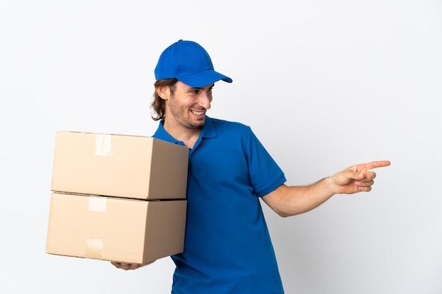 Доставщик, изолированные на белой стене, указывая пальцем в сторону и представляя продукт