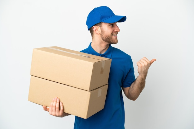Delivery man isolated pointing to the side to present a product