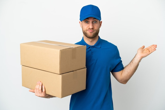 Delivery man over isolated white background having doubts while raising hands