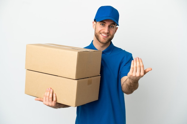 Delivery man over isolated white background inviting to come with hand. happy that you came