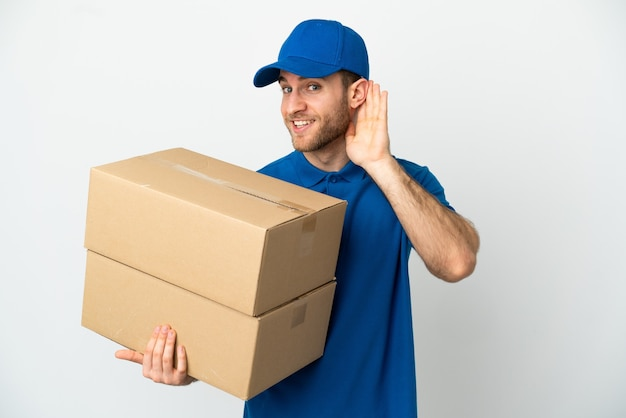 Delivery man over isolated white background listening to something by putting hand on the ear