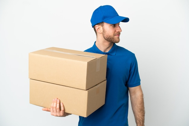 Delivery man over isolated white background looking to the side
