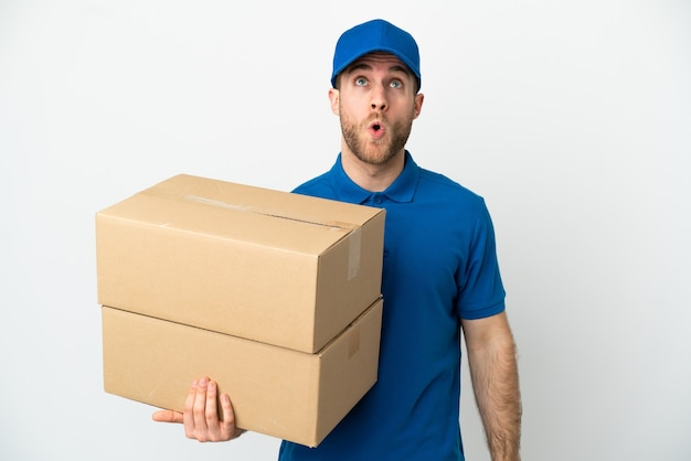 Delivery man over isolated white background looking up and with surprised expression