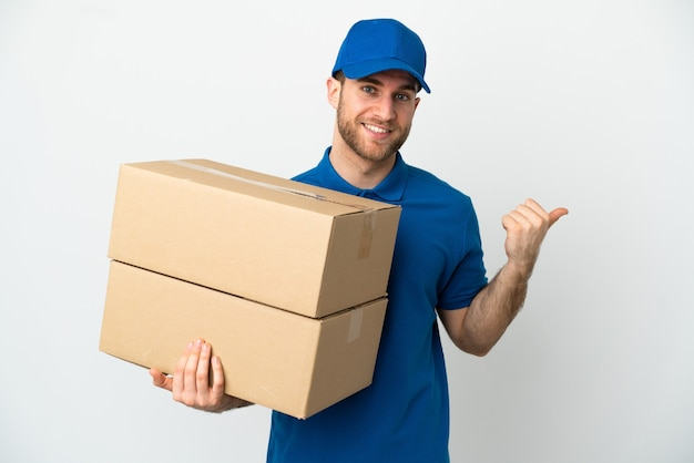 Delivery man over isolated white background pointing to the side to present a product