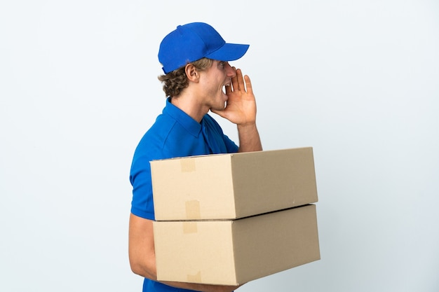 Delivery man over isolated white background shouting with mouth wide open to the side