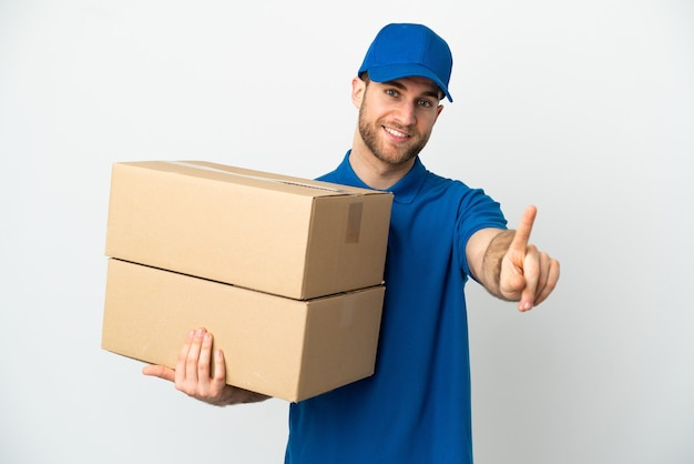 Delivery man over isolated white background showing and lifting a finger
