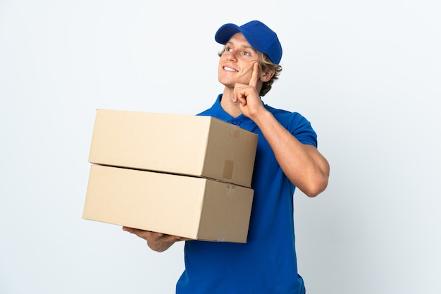Delivery man isolated white background thinking an idea while looking up