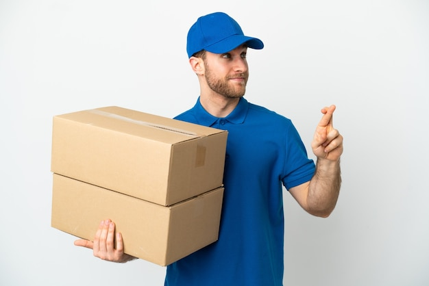 Delivery man over isolated white background with fingers crossing and wishing the best