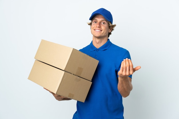 Delivery man on isolated white inviting to come with hand. happy that you came