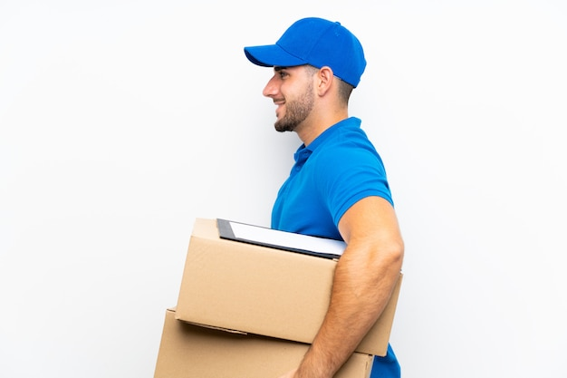 Delivery man over isolated white  looking to the side