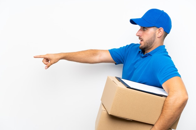 Delivery man over isolated white pointing finger to the side