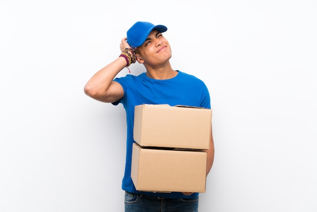 Delivery man over isolated white wall having doubts and with confuse face expression