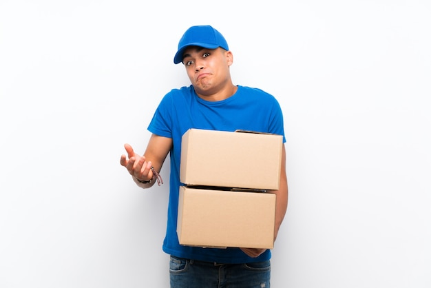 Delivery man over isolated white wall making doubts gesture while lifting the shoulders