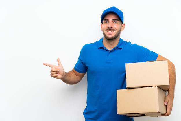 Delivery man over isolated white wall pointing finger to the side
