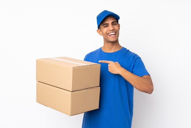 Delivery man over isolated white wall and pointing it