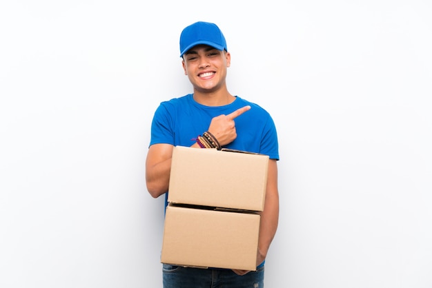 Delivery man over isolated white wall pointing to the side to present a product
