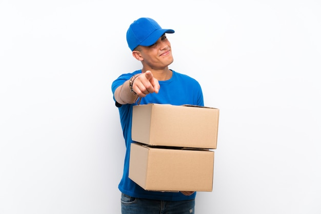 Delivery man over isolated white wall points finger at you with a confident expression