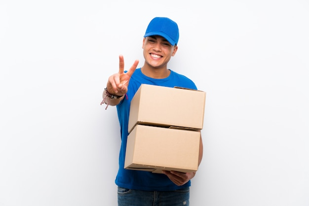 Delivery man over isolated white wall smiling and showing victory sign