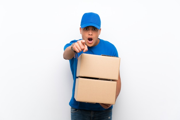 Delivery man over isolated white wall surprised and pointing front