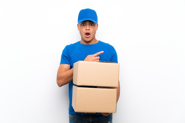 Delivery man over isolated white wall surprised and pointing side