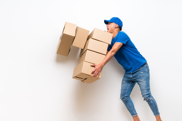Delivery man over isolated white wall with lots boxes and stumbling