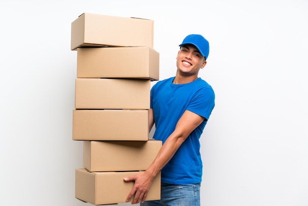 Delivery man over isolated white wall with lots of boxes
