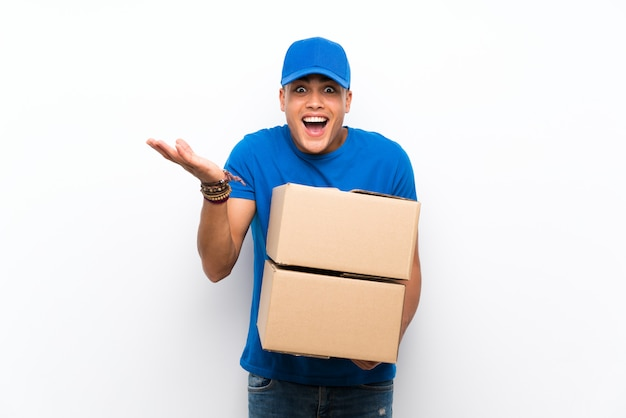 Delivery man over isolated white wall with shocked facial expression