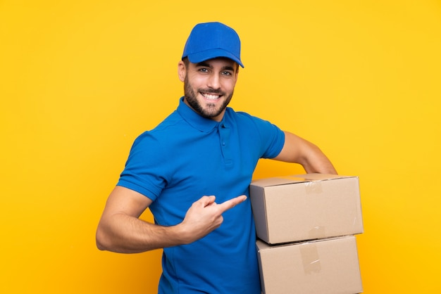 Delivery man over isolated yellow and pointing it