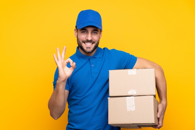Delivery man over isolated yellow wall