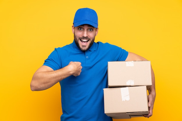 Delivery man over isolated yellow with surprise facial expression