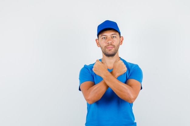 青いtシャツで握りこぶしを交差させたまま配達人