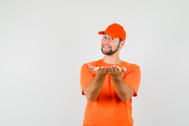 Fattorino che tiene le mani a coppa come offrire qualcosa in maglietta, berretto e sembrare allegro. vista frontale.
