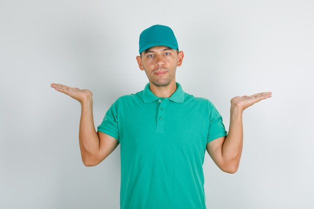 Доставщик держит пустые руки в зеленой футболке с кепкой