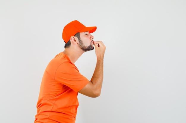 Fattorino che bacia le dita mentre fa un gesto delizioso in maglietta arancione, berretto e sembra felice. .