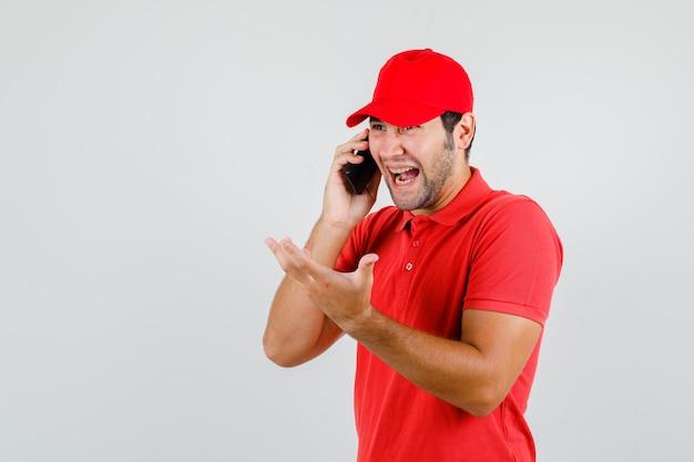 赤いtシャツでスマートフォンで話している間笑っている配達人