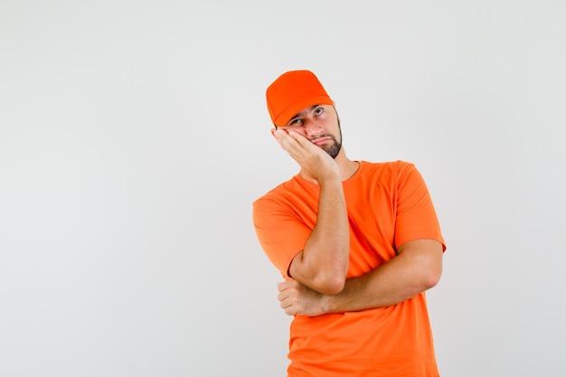 Uomo di consegna guancia appoggiata sul palmo alzato con maglietta arancione, berretto e sguardo pensieroso. vista frontale.