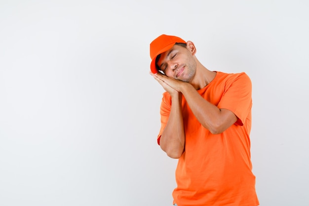 Uomo di consegna che si appoggia sulle palme come cuscino in maglietta arancione e berretto e che sembra pacifico