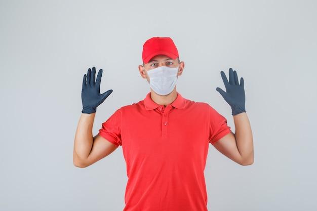 Uomo di consegna alzando le mani in uniforme rossa, mascherina medica, vista frontale guanti.