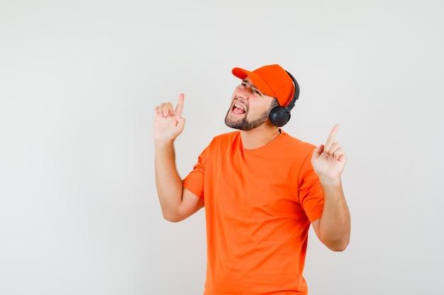Fattorino che ascolta musica con le cuffie in maglietta arancione, berretto e sembra divertito. vista frontale.