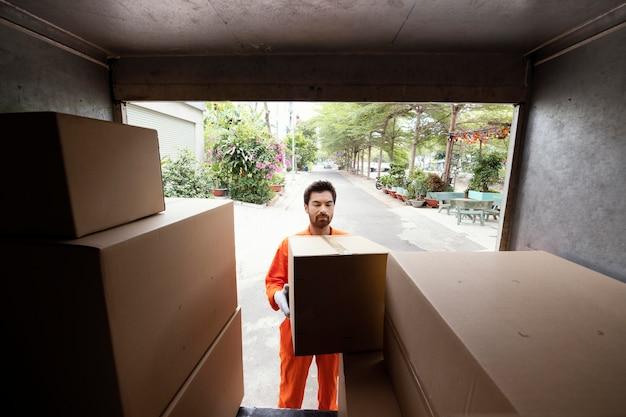 小包箱で車をロードする配達人