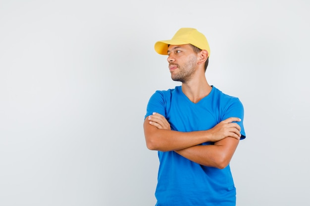 Uomo di consegna che osserva da parte con le braccia incrociate in maglietta blu