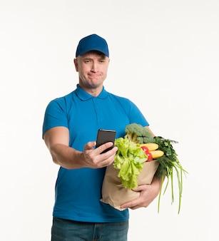 Доставка человек, глядя на смартфон, держа продуктовый мешок