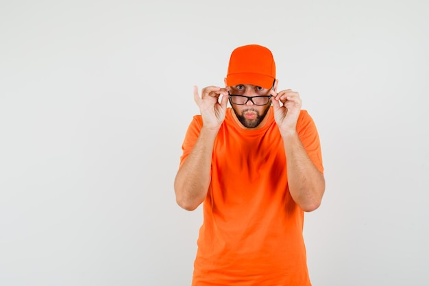 Fattorino che guarda attentamente sopra gli occhiali in maglietta arancione, berretto e sembra sorpreso. vista frontale.