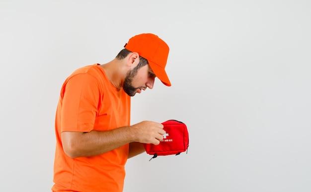 オレンジ色のtシャツ、キャップの応急処置キットを注意深く見ている配達人。