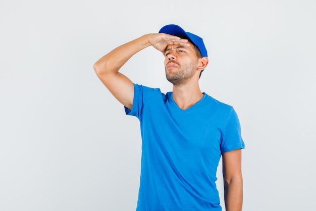 Uomo di consegna che guarda lontano con la mano sugli occhi in maglietta blu